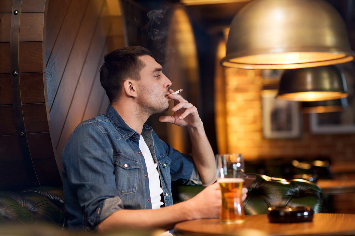 Picture depicting a man continuing to smoke during a robbery at a bar